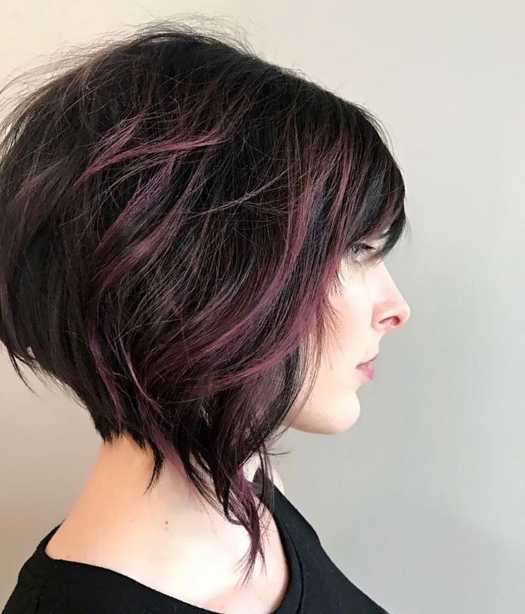 We love this short angled bob and dark purple balayage highlights by Aveda Artis...