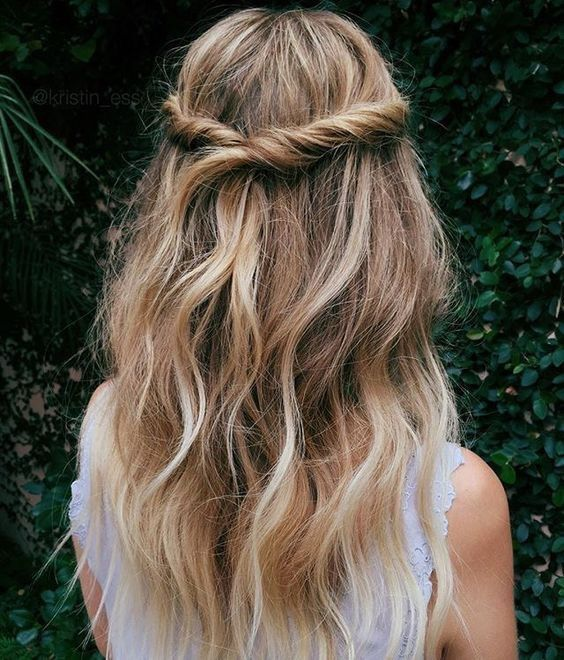 Twisted half-up half-down hairstyle with loose waves for a bohemian and romantic...