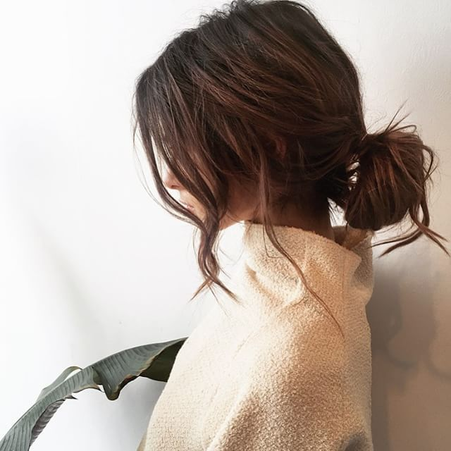 Messy low bun with loose pieces lightly curled