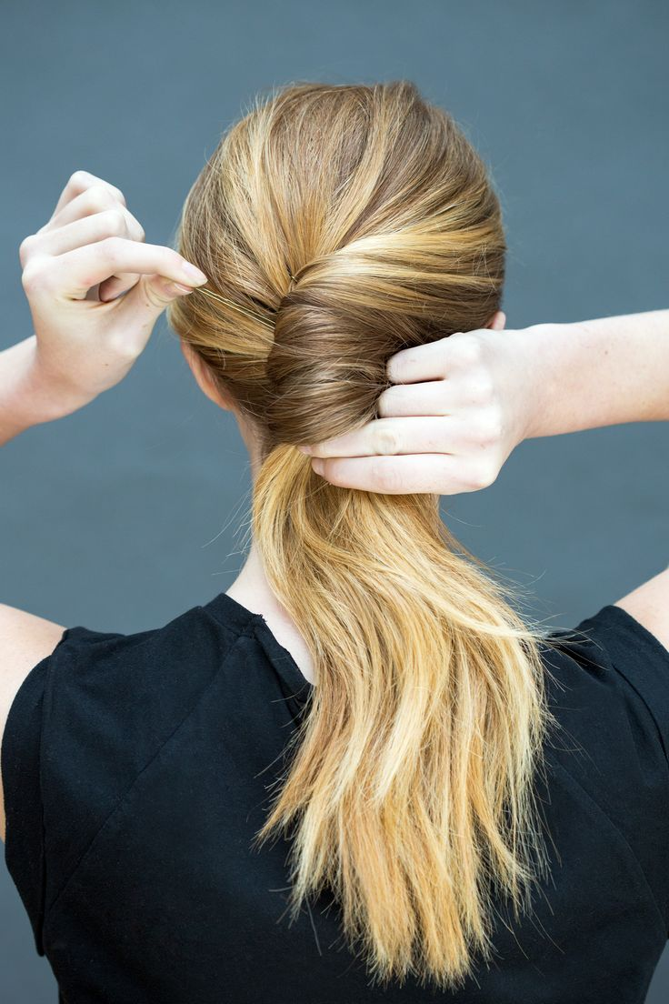 Twist the ponytail into a chignon, and use your other hand to pin with several b...
