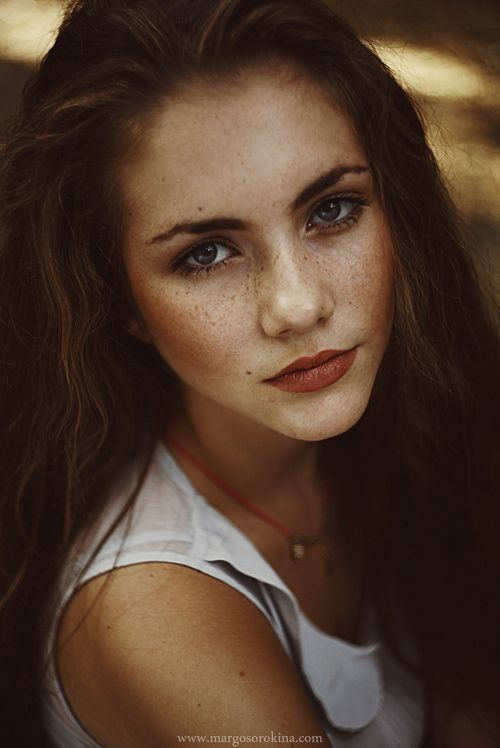 A meek, slightly freckled face, wavy brown hair that tumbles down around her and...